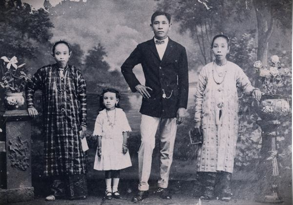 Old family photo from British colonial times. Note the Malay dresses worn by the women.