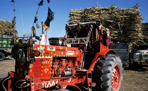 Mechanisation and middlemen: A customised tractor with a trailer full of harvested sugarcane, in Pakistan. flickr / tpmartins