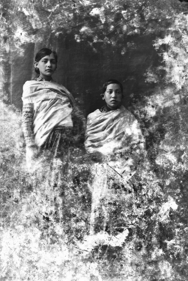 Photographed in the studio of their home, we see Amrit Bahadur Chitrakar's mother (on the right) and her sister (on the left). When Amrit's mother couldn't give birth for ten years, Amrit's father married her sister. Then, both women gave birth to healthy children with a gap of ten months between births. Since both of Amrit's mothers were sisters, he says that he felt no rivalry in the house. This photograph was part of the exhibition 'Facing the Camera: A History of Nepali Studio Photography' at Patan museum.
