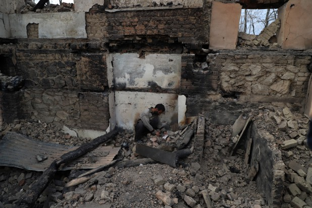 Bhat rummages through the rubble in the corner of his house where he spent long hours of his youth writing poetry.