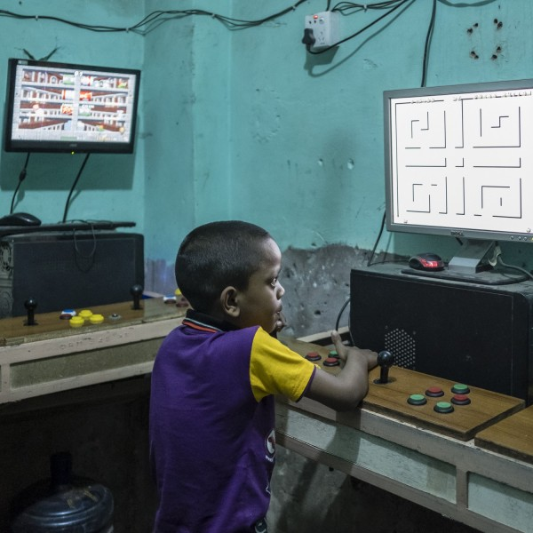 A boy plays an arcade game in the camp's gaming room. Despite a 2008 Supreme Court ruling, many younger generation Biharis do not have Bangladeshi citizenship.