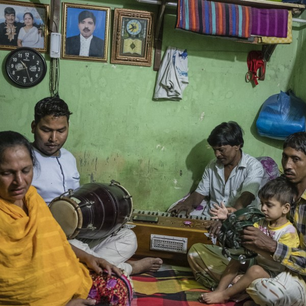 Friends and family gather for a musical recital inside a small bedroom in the camp.